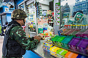 29 MAY 2014 - BANGKOK, THAILAND: A Thai soldier buys a soft drink for a convenience store while on duty at Victory Monument. After a series of protests around Victory Monument earlier in the week, the Thai army Thursday shut down vehicle access to the area, one of the main intersections in Bangkok, and kept people out of the area. Thousands of soldiers surrounded the Monument and effectively locked the area down. There were no protests at Victory Monument for the first time in the week since the coup deposed the elected civilian government.   PHOTO BY JACK KURTZ