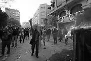 Egyptian protestors chant slogans and hurl insults towards police lines during ongoing demonstrations November 20, 2011 near Tahrir square in central Cairo, Egypt.  Protestors demanding the transition of power from military to civilian control clashed with Egyptian security forces for a second straight day in central Cairo, with hundreds injured and at least 11 protestors killed.  (Photo by Scott Nelson).