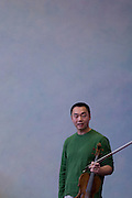 Violist Burchard Tang talks to children at the Meadowbrook School in Kingston, Rhode Island. Tang was a performer in the Kingston Chamber Music Festival in 2008.