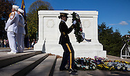A member of the Old Guard carries a wreath to lay beside the Tomb of the Unknown Soldier at Arlington National Cemetery. Numerous veteran groups presented wreaths to  join one that was presented by President Barak Obama as part of Veterans Day observance. (Alan Lessig/Staff)