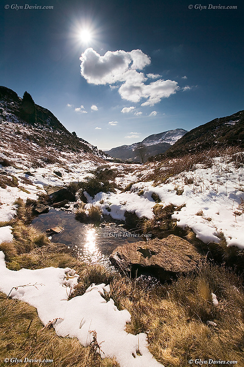 Snow melt water swells the mountain stream in Cwm Bychan, Beddgelert, Snowdonia, Wales. The river runs down to Tremadog Bay, seen bathed in sunlight in the far distance. Light Cumulus clouds float overhead.