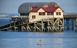 © Licensed to London News Pictures. 13/09/2020. Swansea, UK. A women sails along a calm sea off the coast of Mumbles, Swansea with the RNLI Lifeboat station in the background on a beautiful evening in south Wales. The UK enjoyed a fine weekend of warm and sunny weather. Photo credit: Robert Melen/LNP