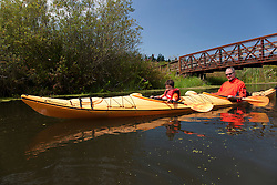 North America, United States, Washington, Bellevue, man and son (age 6) kayaking under bridge in Mercer Slough Nature Park.  MR