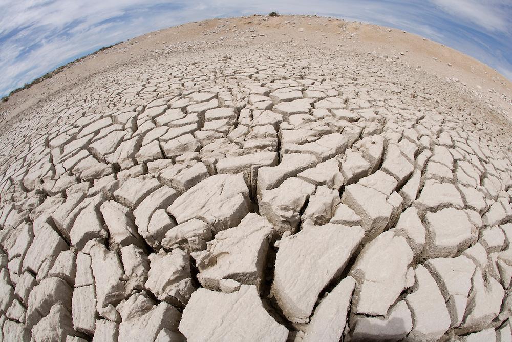 Africa, Namibia, Etosha National Park, Cracked mud in dried water hole at edge of Etosha Pan