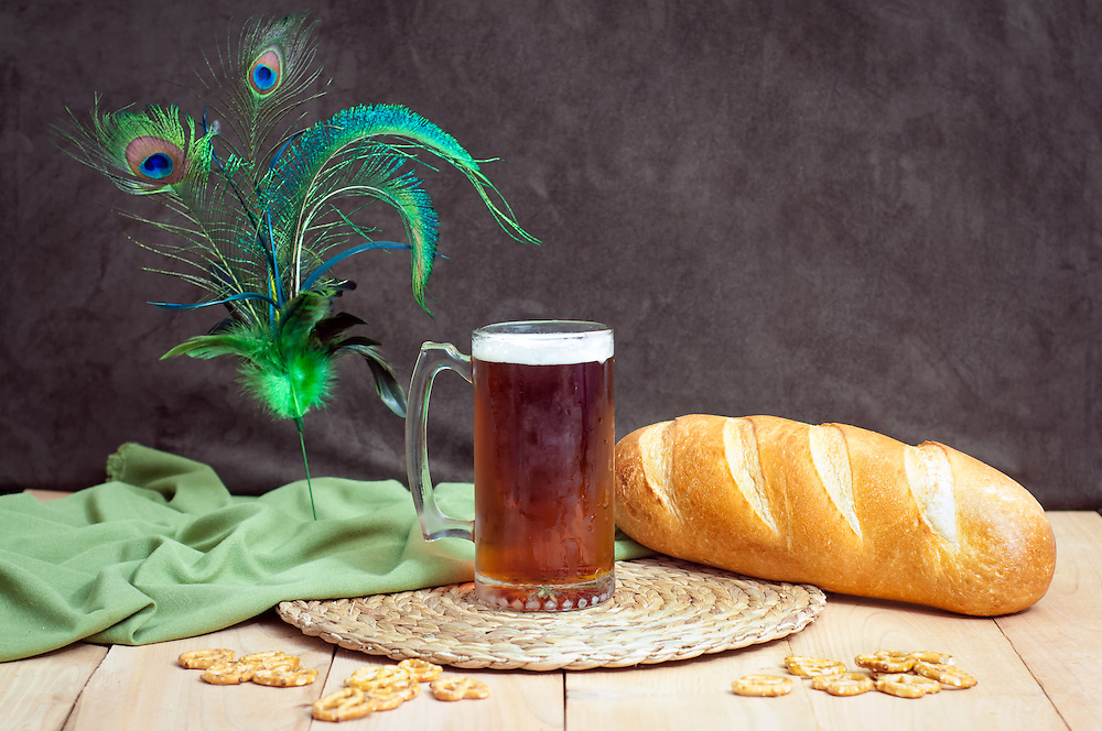 A mug of dark ale with bread and pretzels.
