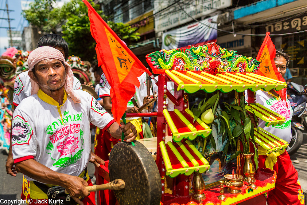 "05 JULY 2014 - BANGKOK, THAILAND:  A man plays a cymbal in Bangkok during a parade for vassa. Vassa, called ""phansa"" in Thai, marks the beginning of the three months long Buddhist rains retreat when monks and novices stay in the temple for periods of intense meditation. Vassa officially starts July 11 but temples across Bangkok are holding events to mark the holiday all week.   PHOTO BY JACK KURTZ"
