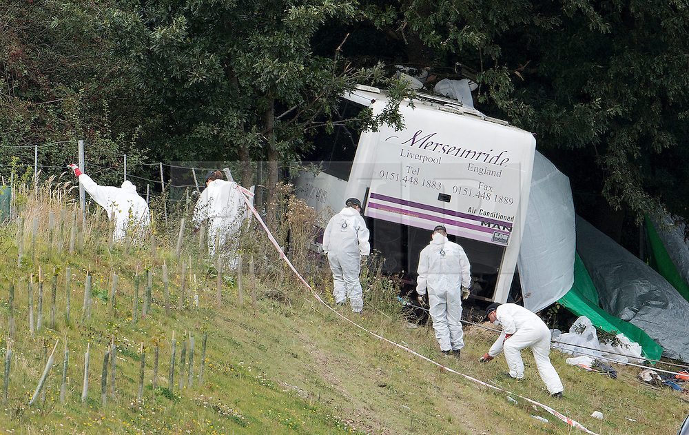 © London News Pictures. 11/09/2012. Hindhead, UK . Forensics performing a finger tip search outside the bus. The scene of a fatal bus crash on the north bound A3 motorway near Hindhead Tunnel, Hindhead, Surrey on September 11, 2012.Three people were killed and a number of others seriously injured when a coach carrying overturned after crashing into a tree. Photo credit: Ben Cawthra/LNP