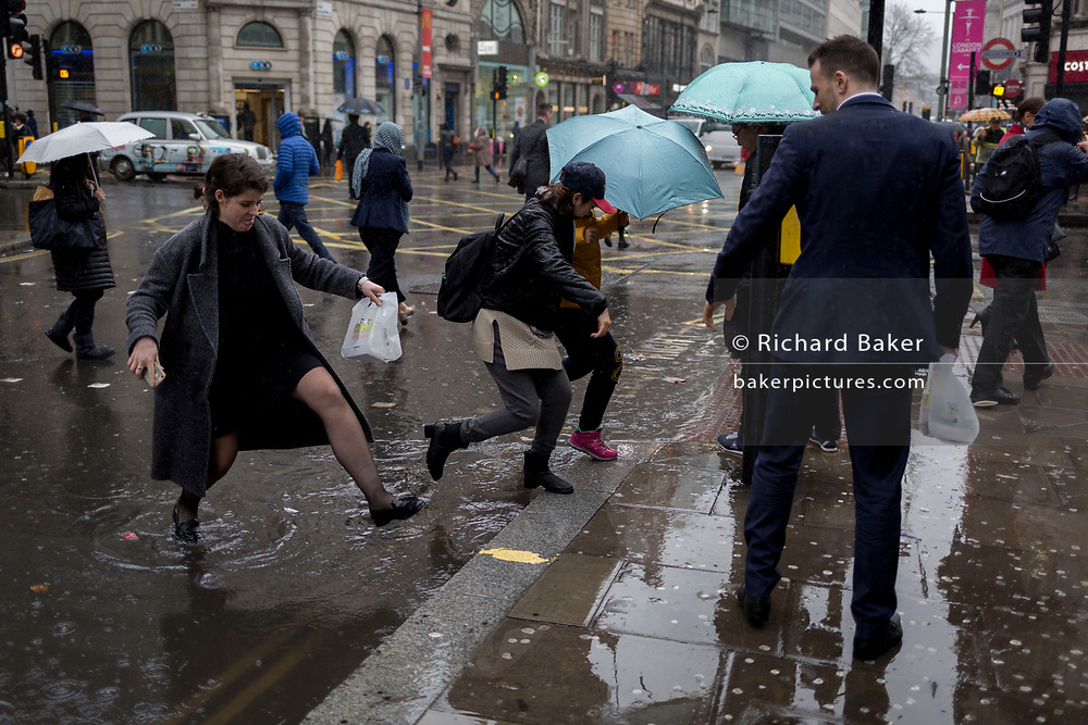 Storm Georgina swept across parts of Britain and in central London, lunchtime office workers were caught out by torrential rain and high winds, on 24th January 2018, in London, England. Pedestrians resorted to leaping across deep puddles at the junction of New Oxford Street and Kingsway at Holborn, the result of overflowing drains. Second in a sequence of two photos.