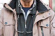 close up of man with glasses hanging from his neck