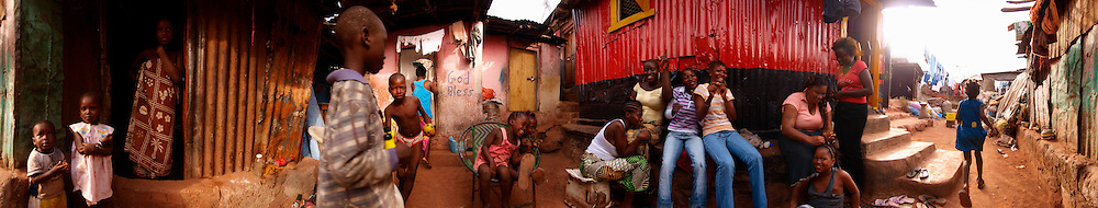 Khadija braiding Madlyn's hair amongst friends and neighbours, Kroo Bay, Freetown, Sierra Leone.