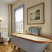 CREAM RIDGE, NJ - OCTOBER 29, 2016: The second floor landing full bathroom has a clawfoot tub and stained glass windows. A doorway leads to a bedroom. 92 Holmes Mill Rd, Cream Ridge, NJ. Credit: Albert Yee for the New York Times