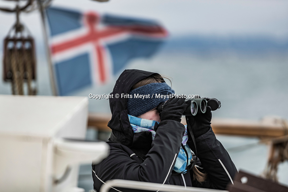 Iceland, April 2019. Danish marine biologist Louise Flensborg on the lookout for whales to take a biopsy of the skin and blubber. Scientists, storytellers and industrial designers work together during the Ocean Missions Iceland scientific sailing expedition aboard Schooner Opal.  The organisation wants to inspire people to take direct action towards ocean conservation, by combining science and education with exploration and adventure. Photo by Frits Meyst / Meystphoto.com