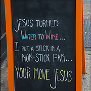 "Blackboard humorous  outdoor wine store sign. 'Jesus turned Water to Wine ...I Put a Stick in a Non-Stick Pan ... Your Move Jesus""."
