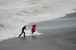 © London News Pictures. 05/12/2015 Aberystwyth, Wales, UK. Children play a dangerous game of dodging the waves on the beach at Aberystwyth. The fourth named storm of the season, Storm Desmond, picks up strength and begins to batter the coast at Aberystwyth, west Wales.The Met Office has issued yellow warnings for the gale force winds,  with gusts of up to 70mph in places on the Irish Sea coast.. Photo credit: Keith Morris/LNP