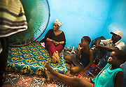 Liberian national Nina Jallah (left) sits with her children and friend Michael Johnson, also Liberian, in the room where Nina lives with her family in Dakar, Senegal on Thursday July 16, 2009. Nina says she's not following the Charles Taylor trial and wishes people could just move on..