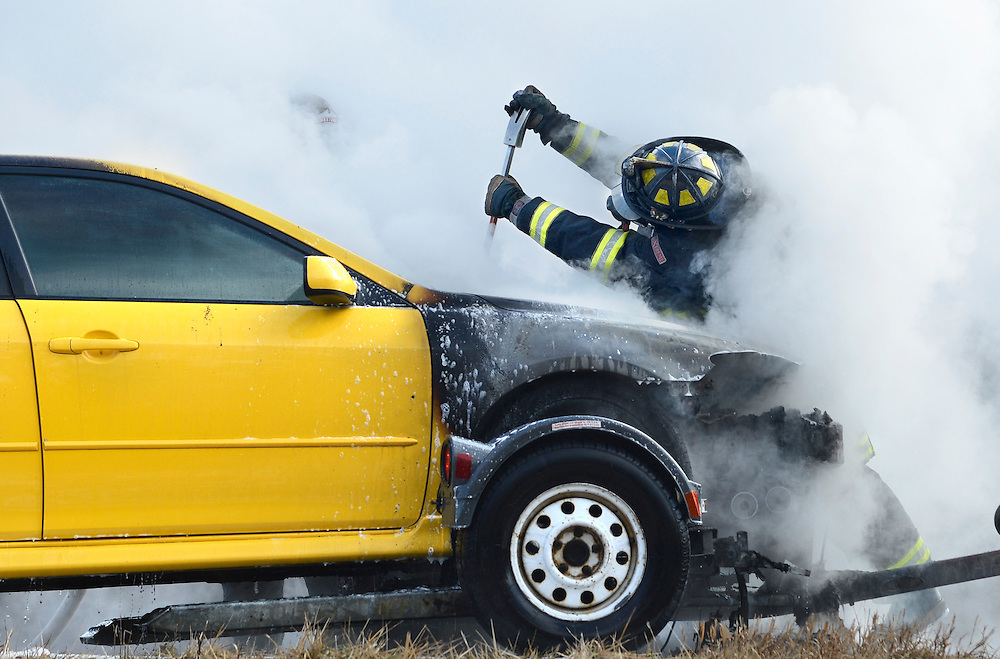 A LImestone firefighter tries to force open the hood of a car burning along I-474 Tuesday.