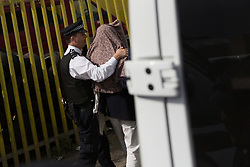 © Licensed to London News Pictures. 05/06/2017. LONDON, UK.  A covered woman is led out of an address on Ripple Road in Dagenham into a police van outside. Police carried out a raid at a Dagenham address early this morning in connection with the London Bridge terror attacks and residents reported hearing gun shots.  Photo credit: Vickie Flores/LNP