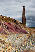 An old chimney rises near a pink rock at Achada do Gamo, on the abandoned mining complex of S.Domingos