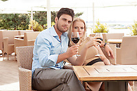 Portrait of young couple having red wine at outdoor restaurant