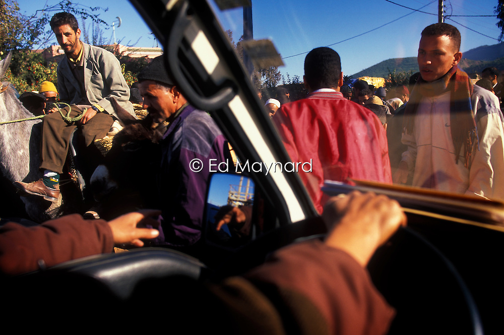 Driving through bustling crowds during market day at Ourika, Morocco.