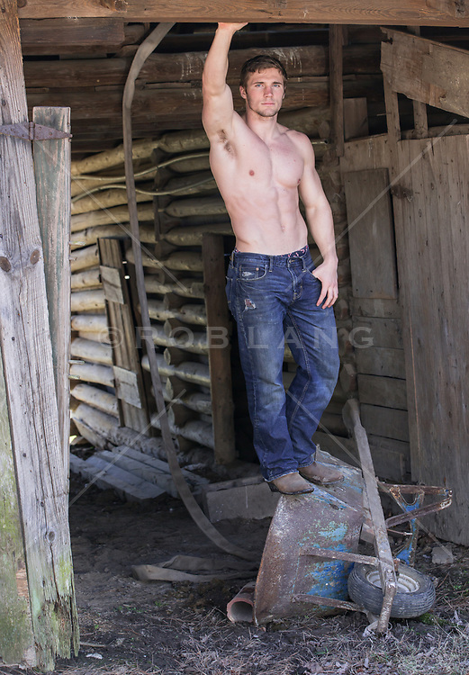 shirtless muscular man standing on a wheel barrel by a barn