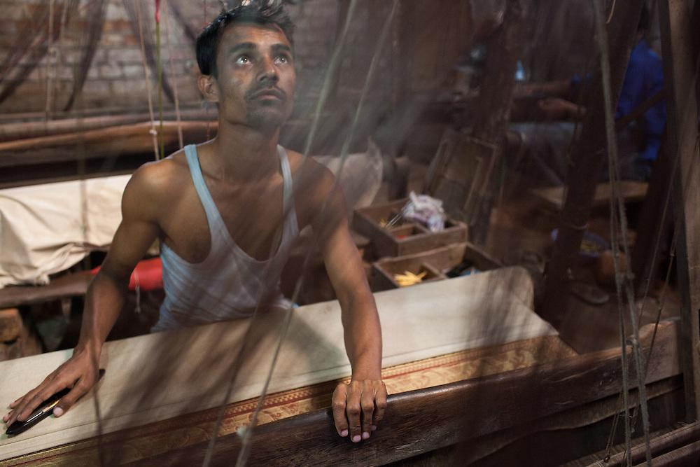 A worker operates the card punch loom that weaves traditional Jamdani sari in Mirpur Benarashi Palli, Dhaka, Bangladesh, a poor Bengali neighborhood.
