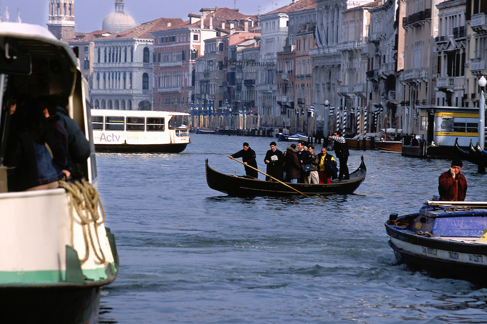 Everyday water traffic on the Grand Canal: vaporetti, traghetto with standing passengers, motor launch;