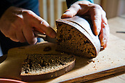 Aivars  Radzins, a forester and beekeeper, slices a loaf of bread at his home in Vecpiebalga, Latvia. (Aivars Radzins is featured in the book What I Eat: Around the World in 80 Diets.)