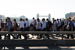 © Licensed to London News Pictures. 24/07/2018. London, UK.  Commuters walk to work over London Bridge during another day of hot and sunny weather in the capital.  Photo credit: Vickie Flores/LNP