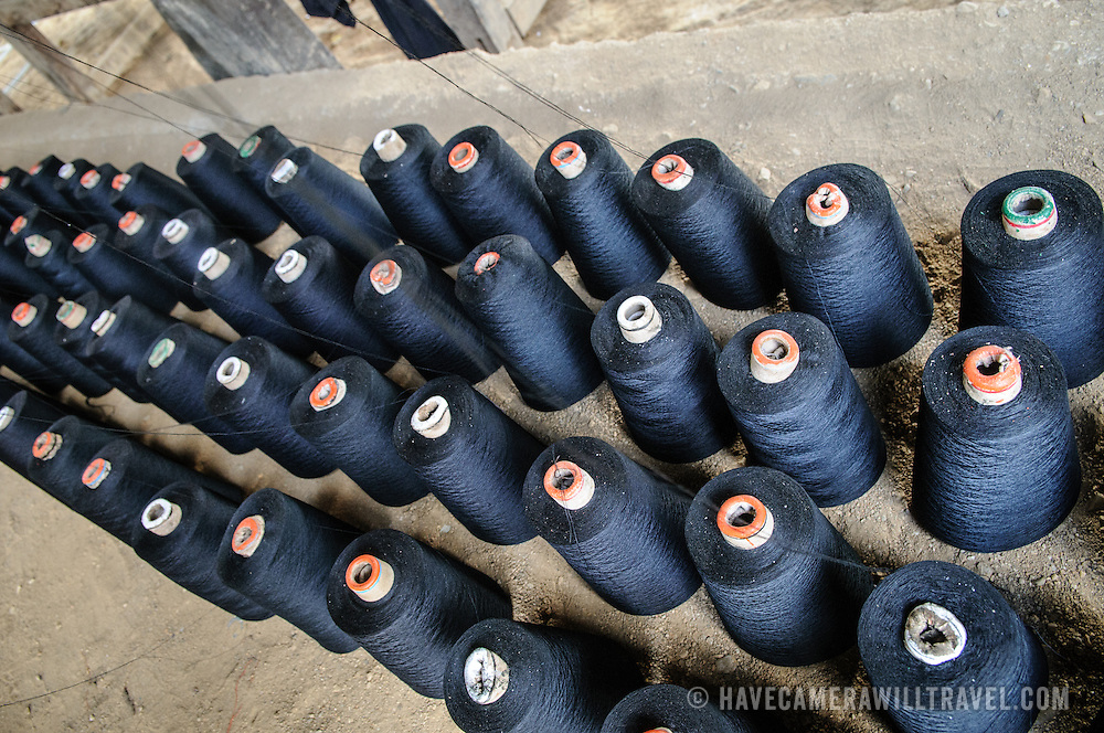 Rows of spindles of dark thread sit on racks at a weaver's house in northeastern Laos.