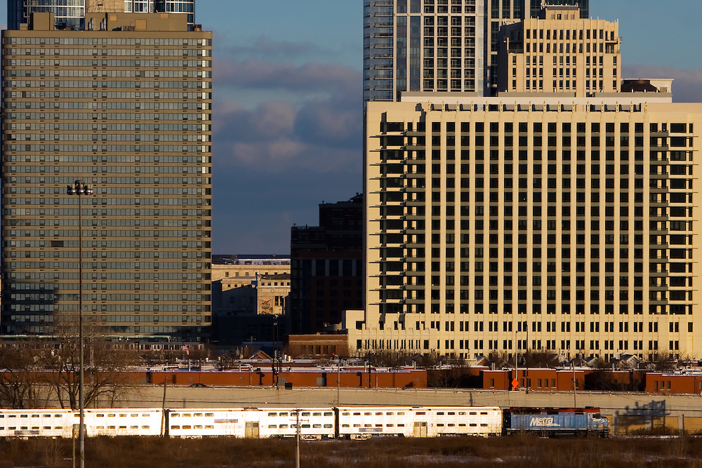 An outbound Metra Rock Island line train passes under several buildings along the Chicago lakefront as winter lake effect snow clouds hang over Lake Michigan in the distance.