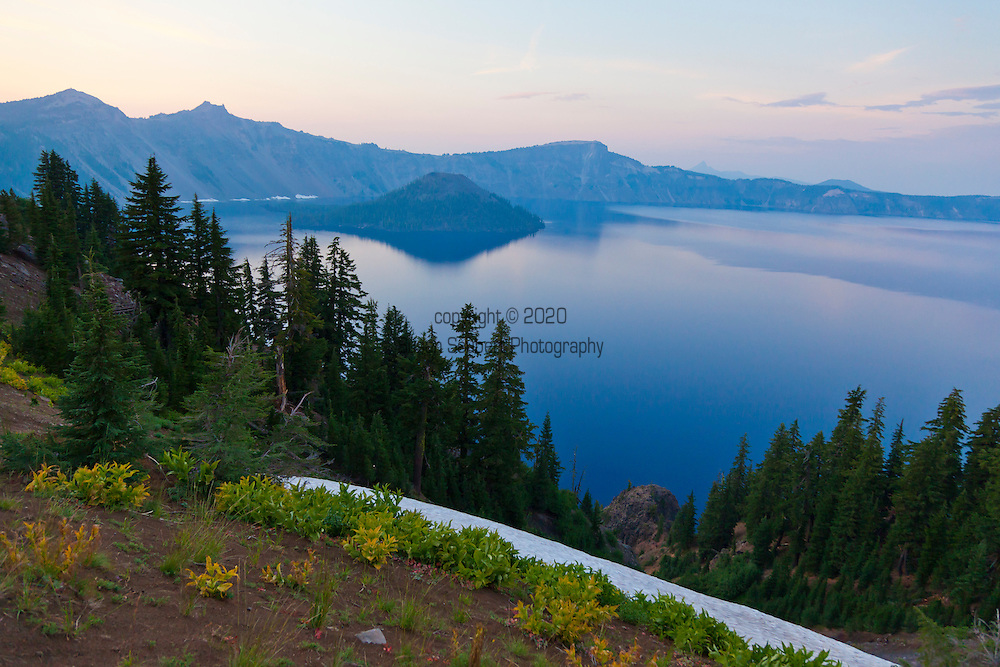 Crater Lake National Park, the only National Park in the state of Oregon, attracts some 482,000 people annualy. The lake itself is 592 meters (1,943ft) deep and is the deepest lake in the United States.  The park was founded in 1902 and seeks to preserve the natural and cultural resources.  Crater Lake lies in a caldera, or volcanic basin, created when Mt. Mazama collapsed around 7,700 years ago.  The clarity and blueness of the water are unique to this geologic area.  The lake is filled almost entirely by melted snow.  The lake is only accessibly by one trail, the Cleetwood Cove Trail, which leads down to the water for access to the tourist boats.  Crater Lake at sunset.