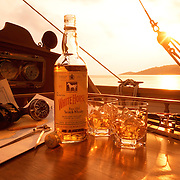 Beauty bottle and two glasses on the deck of a boat at sea including sunglasses, binoculars and map and nautical tools Ray Massey is an established, award winning, UK professional  photographer, shooting creative advertising and editorial images from his stunning studio in a converted church in Camden Town, London NW1. Ray Massey specialises in drinks and liquids, still life and hands, product, gymnastics, special effects (sfx) and location photography. He is particularly known for dynamic high speed action shots of pours, bubbles, splashes and explosions in beers, champagnes, sodas, cocktails and beverages of all descriptions, as well as perfumes, paint, ink, water – even ice! Ray Massey works throughout the world with advertising agencies, designers, design groups, PR companies and directly with clients. He regularly manages the entire creative process, including post-production composition, manipulation and retouching, working with his team of retouchers to produce final images ready for publication.