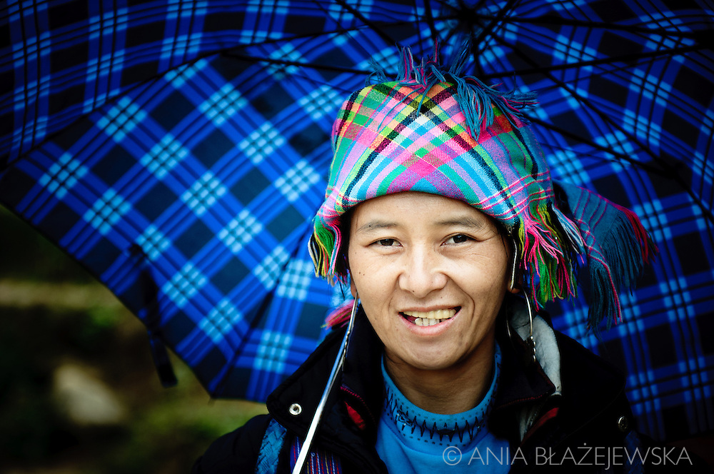 Vietnam, Sapa. Portrait of a Hmong woman holding checkered pattern umbrella.