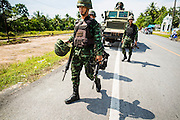 11 JULY 2013 - RAMAN, YALA, THAILAND:  Thai soldiers carry the weapons and equipment of their colleagues injured in an IED attack Thursday morning. Eight soldiers were injured when the IED exploded under a Thai Army truck carrying soldiers back to their camp after they finished a teacher protection mision. The army routinely dispatches soldiers to protect teachers and Buddhist monks, who have been targeted by Muslim insurgents as representatives of the Bangkok government. More than 5,000 people have been killed and over 9,000 hurt in more than 11,000 incidents in Thailand's three southernmost provinces and four districts of Songkhla since the insurgent violence erupted in January 2004, according to Deep South Watch, an independent research organization that monitors violence in Thailand's deep south region that borders Malaysia.   PHOTO BY JACK KURTZ