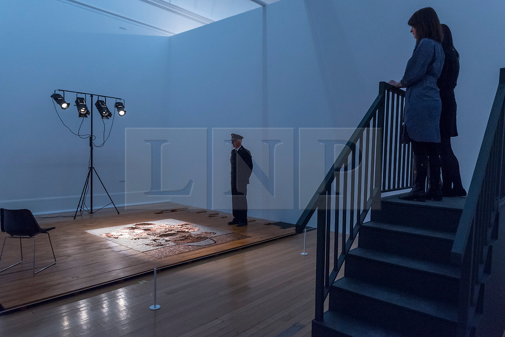 """© Licensed to London News Pictures. 01/04/2019. LONDON, UK.  """"Bureau de Change"""", 1987, by Rose Finn-Kelcey is unveiled at Tate Britain.  Coinciding with """"The EY Exhibition:  Van Gogh and Britain"""", the live installation consists of £1,000 worth of coins laid out on the floor in the image of Vincent Van Gogh's """"Sunflowers"""".  The installation is overseen each day by an actor posing as a security guard, with visitors viewing the scene from a platform and will be in place 1 Aptil to 11 August 2019.  Photo credit: Stephen Chung/LNP"""