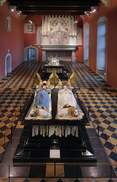 Tombs of Jean sans Peur, or John the Fearless, 1371-1419, Duke of Burgundy, and his wife Marguerite de Baviere, or Margaret of Bavaria, 1363- 1423, 1443-70, by Jean de la Huerta and Antoine le Moiturier, and behind, tomb of Philippe le Hardi, or Philip the Bold, 1342-1404, Duke of Burgundy, 1381-1410, by Jean de Marville, Claus Sluter et Claus de Werve, in the Grande Salle du Palais des ducs de Bourgogne, or Salle des Gardes, in the Musee des Beaux-Arts de Dijon, opened 1787 in the Palace of the Dukes of Burgundy in Dijon, Burgundy, France. The tombs consist of painted alabaster effigies with lions and angels, and below, figures of pleurants or weepers among Gothic tracery. The Guardroom, a large ceremonial and banquet hall, was built 1450-55 by Philippe le Bon, or Philip the Good, 1396-1467, Duke of Burgundy, in Flamboyant Gothic style. The tombs were originally from the Chartreuse de Champmol, or Chartreuse de la Sainte-Trinite de Champmol, a Carthusian monastery which was sacked in the French Revolution and the tombs moved to Dijon cathedral then here in 1827. The effigies are 19th century reconstructions, the originals being destroyed in the French Revolution. Picture by Manuel Cohen