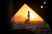 The glow of the setting sun is seen from inside a minaret dotted with bullet holes located in a West Mosul neighbourhood recently liberated from Islamic State control by Iraqi forces, on June 25, 2017. Smoke billows in the background as a group of Islamic State fighters launch a counter attack in a nearby neighbourhood, setting fire to houses, causing thousands of civilians to flee in fear of a resurgence of the terror group.