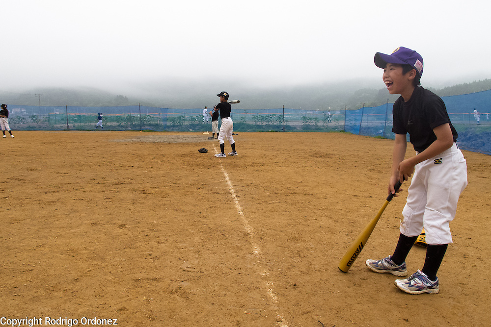 Children of Otomo baseball team practice on the school grounds.