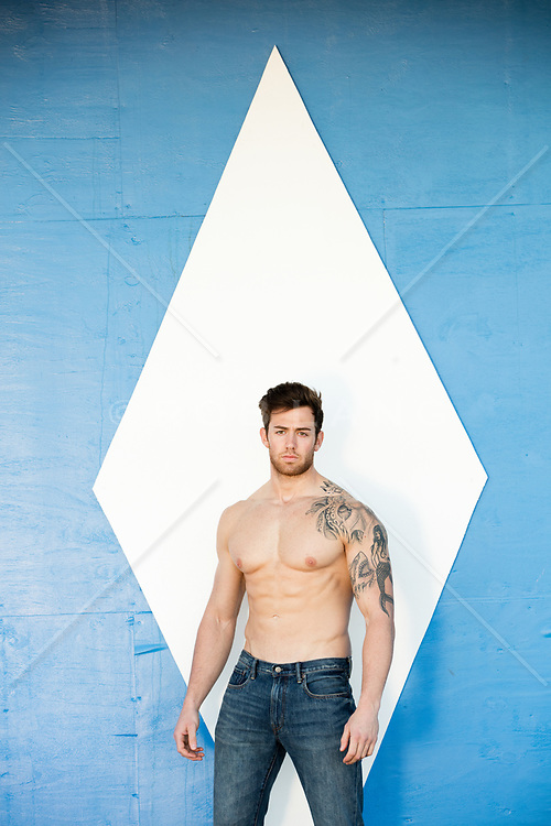 shirtless muscular man with a tattoo against a wall with a diamond shape