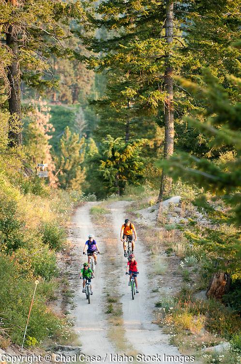 Family riding mountain bikes on trails at Bogus Basin Resort near Boise, Idaho.  Model released.