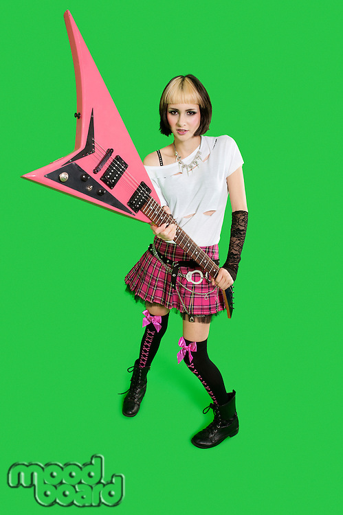 Beautiful punk woman with guitar over green background