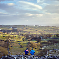 A photograph of two people sat on the limestone pavement enjoying the view of sunset above Malham Cove in the Yorkshire Dales National Park, England
