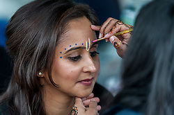 © Licensed to London News Pictures. 05/09/2015. Watford, UK. A woman has gopi dots applied during her visit to the biggest Janmashtami festival outside of India at the Bhaktivedanta Manor Hare Krishna Temple in Watford, Hertfordshire.  The event celebrates the birth of Lord Krishna and the festival  includes music, dance, food, dramas and more. Photo credit : Stephen Chung/LNP