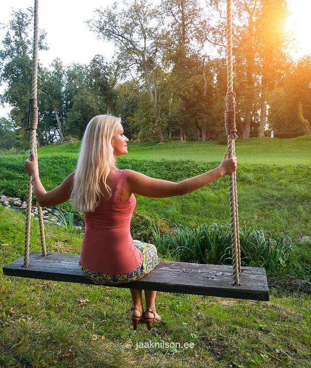 Blond woman sitting on rustic swing.