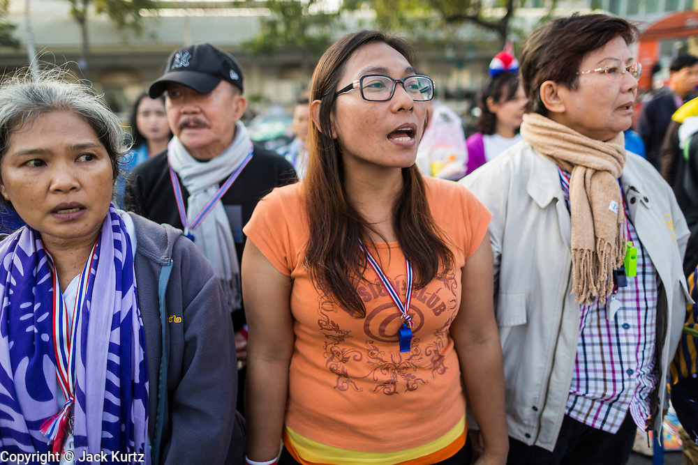 "01 JANUARY 2014 - BANGKOK, THAILAND:  Anti-government protestors sing the Thai national anthem and chant ""Long Live the King!"" during a special merit making ceremony in the protest camp. Thousands of anti-government protestors are camped out at Democracy Monument in central Bangkok protesting against the government of Yingluck Shinawatra. The protest leader, Suthep Thaugsuban, has called for residents of the Thai capital to rise up against Yingluck. He has promised to shut the city of 12 million down in his final push to overthrow the government. About 100 members of the Thailand's Buddhist clergy visited the protest site Wednesday morning for a special New Year's day merit making ceremony for the protestors.    PHOTO BY JACK KURTZ"