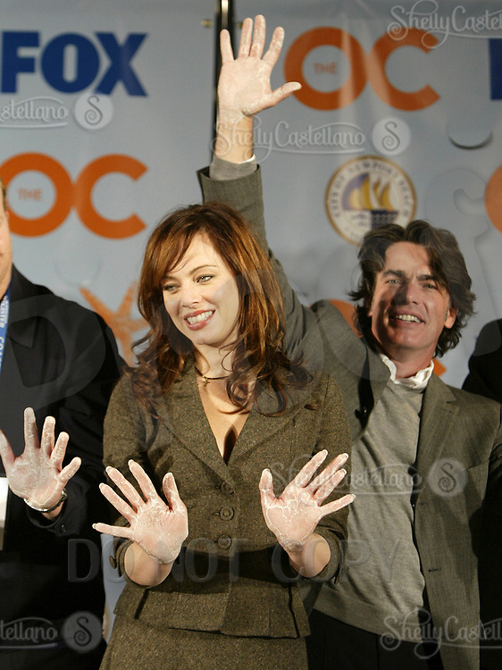 Oct 28, 2004; Newport Beach, CA, USA; Cast Members MELINDA CLARKE & PETER GALLAGHER wave to the crowd with cement hands for the FOX hit TV show 'The OC' visited the Balboa Penninsula in Newport Beach to get a Key to the City and be immortalized in cement with thier hand prints to be placed at the enterance to the Historic Balboa Pavillion.  Mandatory Credit: Photo by Shelly Castellano/ZUMA Press.