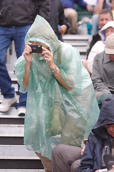 Liverpool, England - Wednesday, June 13, 2007: A fan takes a photograph in the rain during day two of the Liverpool International Tennis Tournament at Calderstones Park. (Pic by David Rawcliffe/Propaganda)