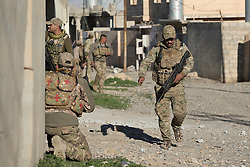 Licensed to London News Pictures. 20/02/2017. Albu Saif, Iraq. An Iraqi Emergency Response soldier runs past a street as colleagues provide cover in the village of Albu Saif during the offensive to retake western Mosul from Islamic State militants.<br /> <br /> The settlement of Albu Saif is located on high ground overlooking Mosul Airport and as such is a strategic point that needs to be taken as part of the operation to retake the western side of Mosul. Photo credit: Matt Cetti-Roberts/LNP