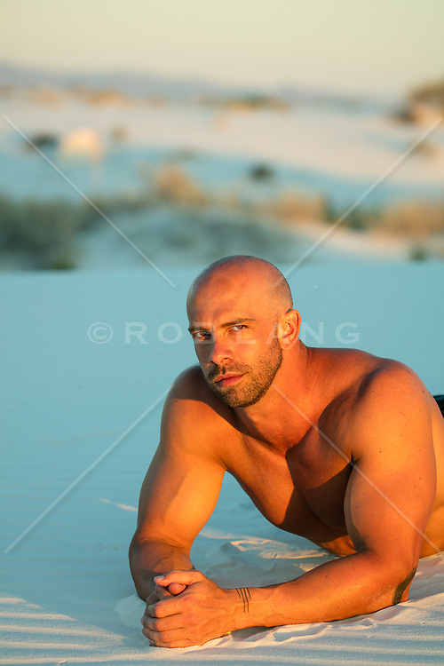 bald handsome man outdoors at sunset in a sand dune